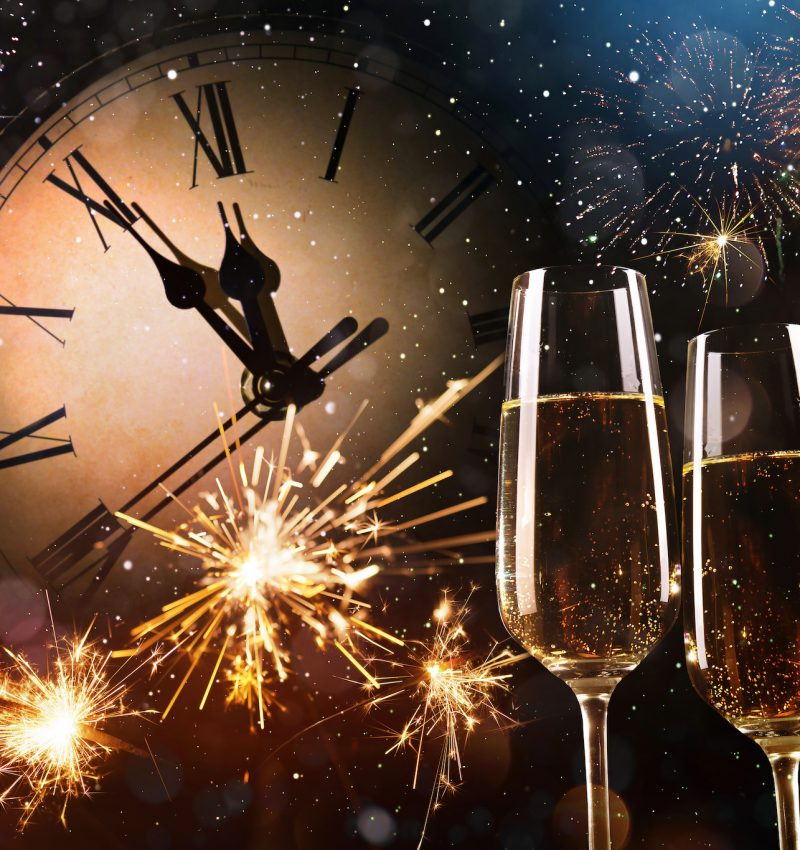 New Years Eve celebration background. Toast with fireworks and champagne at midnight